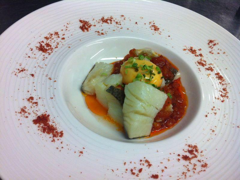 Bacalao confitado con tomate provenzal y yema de corral.